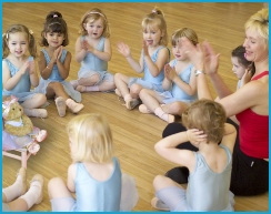 Jill Bridger and Melody Bear dancers sitting in a circle clapping