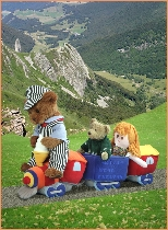 Photo of Milligan Bear driving a toy train with a rag doll across a mountain range