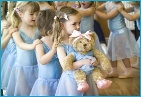 Young children in a long line with their hands on each others shoulders learning to dance