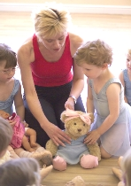 Young dancers help dress dancing teddy, Melody Bear, in Jill Bridger's pre-school lessons