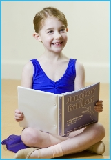 Photo of junior ballet ballerina looking at a book