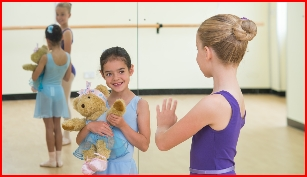Junior ballet grade dancer waves to pre-school dancer