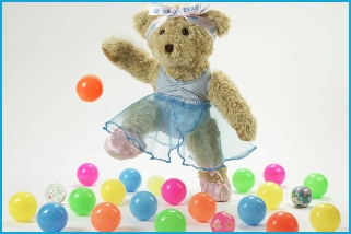 Photo of Melody Bear dancing with coloured bouncy balls