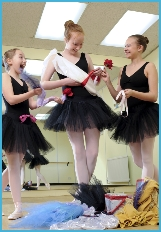 Senior ballet students creating a costume out of ribbons and flowers
