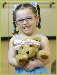 Photo of a pre-school dancer holding Melody Bear