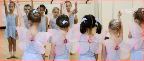 Photo of ballet children in wings and holding wands looking at themselves in a mirror