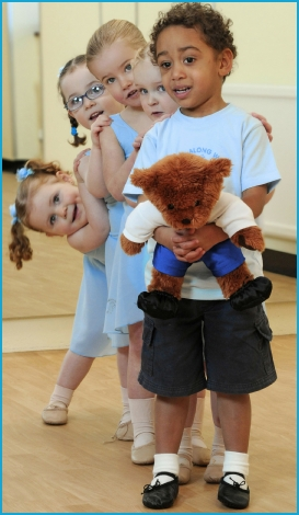 Girls and boys dancing with Milligan Bear