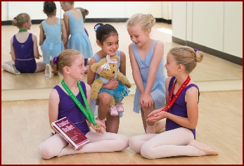 Ballet dancers looking at their medals